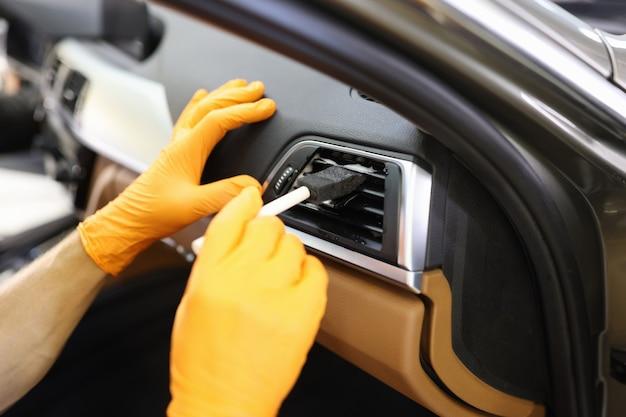 고무 장갑을 낀 마스터 수리공은 작업장 클로즈업에서 브러시로 자동차 에어컨을 청소합니다. 오토 디테일링 컨셉