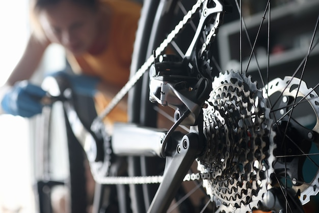 Master repairman repairing bicycle in workshop closeup