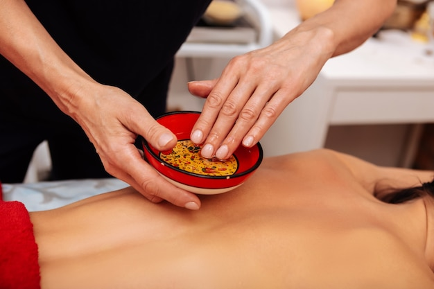 Master in salon. attentive master of massage dipping hand into bowl with special oil before processing client back