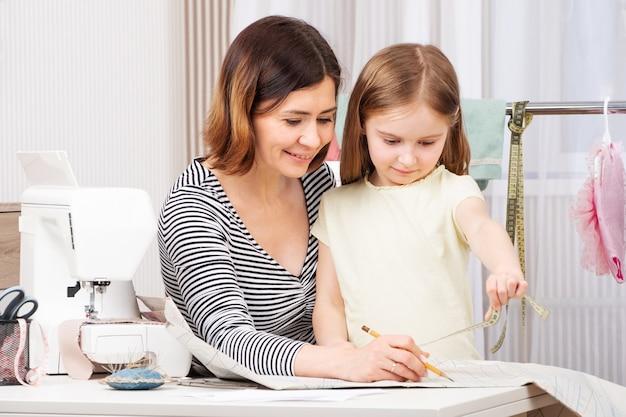 Мастер-швея учит девочку шить