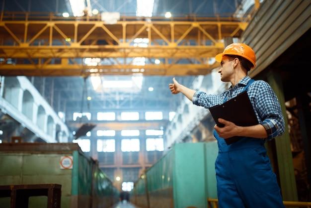 マスターは金属工場のクレーンオペレーターに親指を立てます。金属加工産業、鉄鋼生産の工業生産