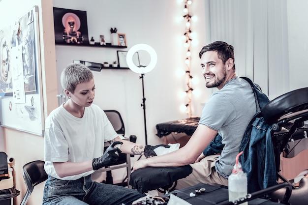 マスタースプレーアルコール。特別な椅子に座ってタトゥーを詰める前に手でスプレーされる黒髪のクライアントの笑顔
