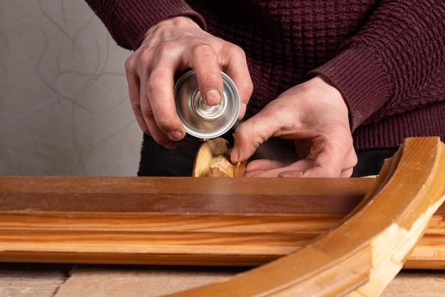 Мастер распыляет лак на реставрацию деревянной двери