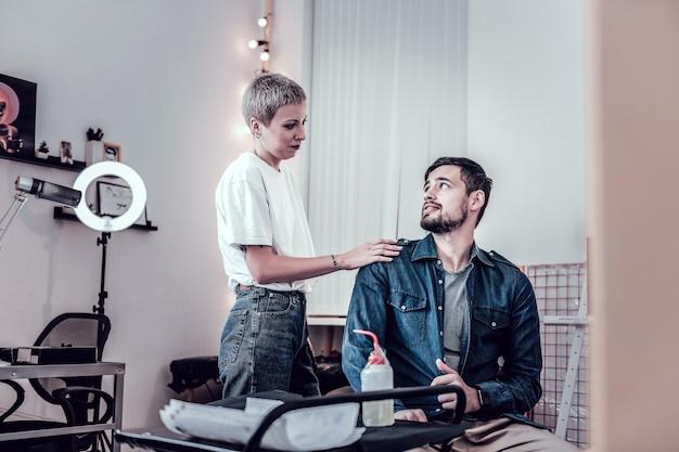 マスターは近くにいます。彼女のクライアントを落ち着かせ、彼の肩に手を置く快適な短い髪のタトゥーマスター