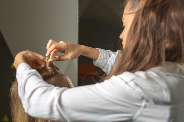 マスタースタイリストは美容院で若いブロンドの女性にヘアスタイルをします