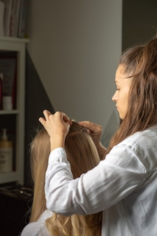 マスタースタイリストが美容院で長髪の愛らしい女性にスタイリングをします