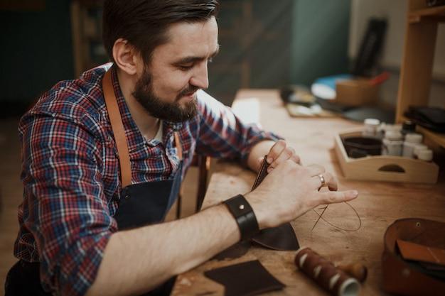 Master tanner works in workshop