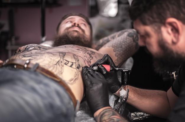 マスタータトゥー師はタトゥースタジオを着色するタトゥーを示しています。