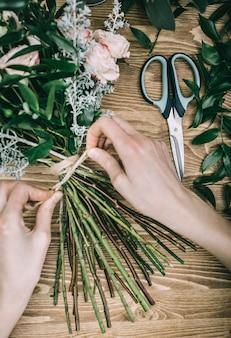 花の茎の周りに紐を結ぶマスター