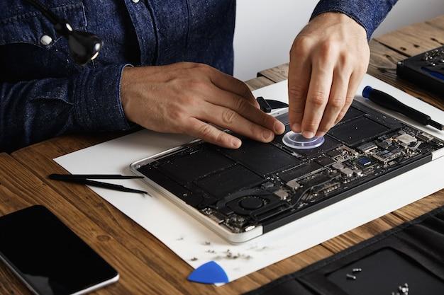 Мастер использует небольшую присоску, чтобы заменить элементы батареи сломанного ноутбука, чтобы починить и очистить его в своей лаборатории с помощью специального набора инструментов на деревянном столе вокруг.