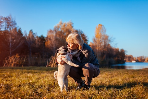Master walking pug dog in autumn park by river happy woman kissing pet