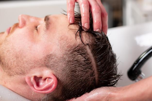 Мастер моет голову клиента в парикмахерской, парикмахер делает прическу для молодого человека.