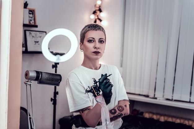 Tシャツを着たマスター。タトゥーマシンを手に持ち、仕事に自信を持っているボーイッシュな女性マスター