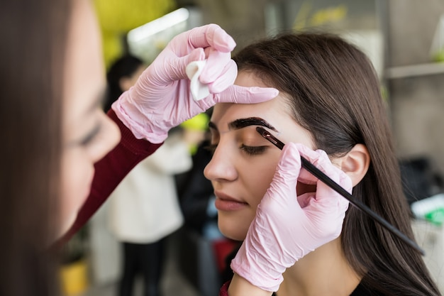 Master in white gloves work at balck eyebrows in beauty salon