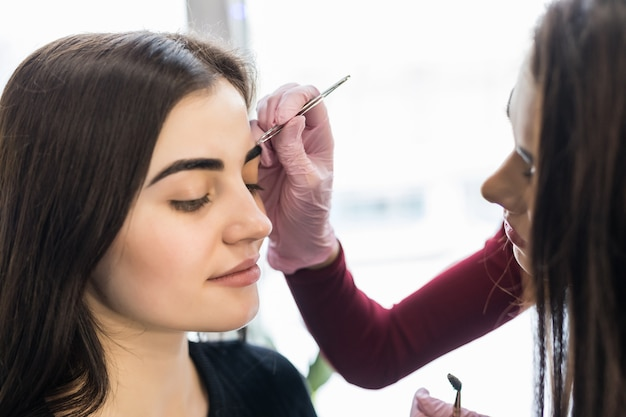 Master in white gloves work at balck eyebrows technique in beauty salon