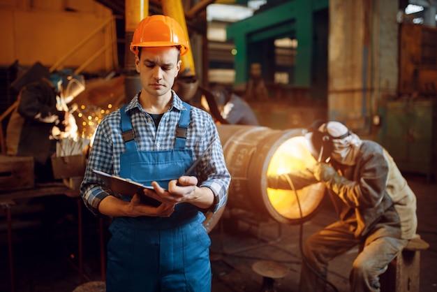 Мастер с ноутбуком и сварщик на заводе