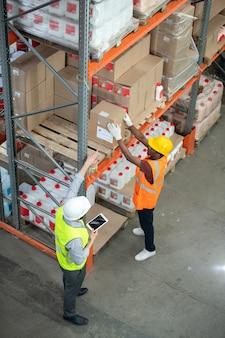 Мастер с планшетом разговаривает с погрузчиком во время работы на складе