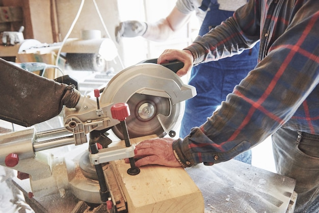 Master in a work suit using a grinder on a sawmill.