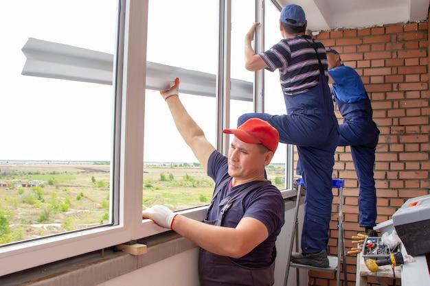 マスターワーカーは家の建物に窓枠の修理をインストールします。