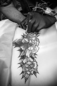 タトゥースタジオでプロのタトゥーマシンガンに取り組んでいるマスター。