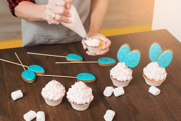 Masterclass of preparing cupcakes with white cream on wooden table