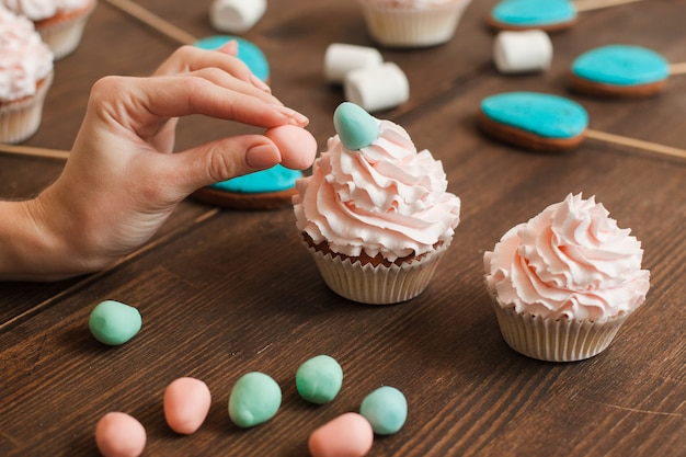 Masterclass of preparing decorated cupcakes with white cream on wooden table