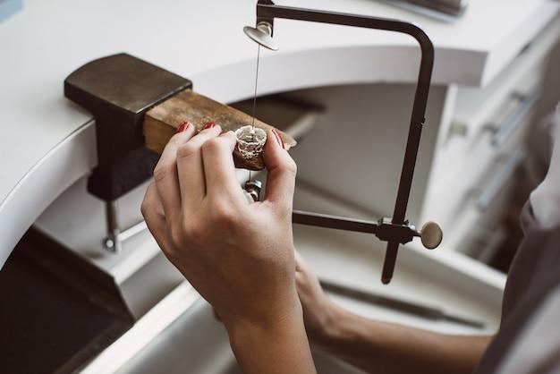 그녀의 반지에서 작업하는 여성 보석상 손의 마스터 손 클로즈업