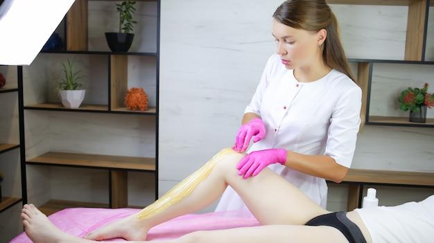 설탕 제모의 마스터는 그의 사무실에서 모델과 함께 그녀의 다리에 설탕 페이스트를 바르고 있습니다.