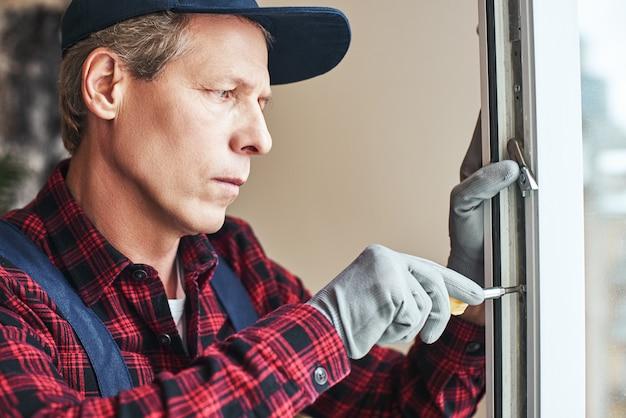 Мастера работают крупным планом старшего разнорабочего, устанавливающего новые окна