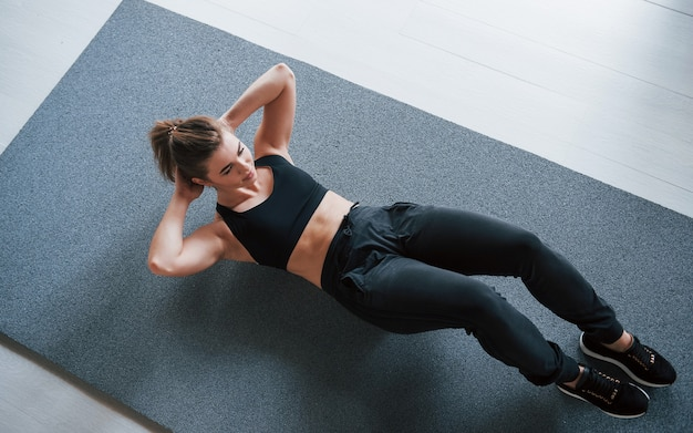 On the mat. doing abs on the floor in the gym. beautiful female fitness woman.