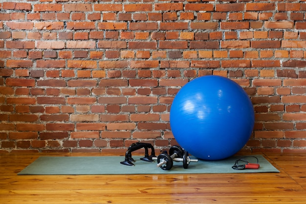 Mat, fitball, rope, dumbbells and stand push-upse on floor in gym