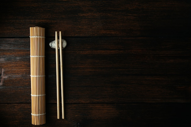 Mat for rolls and chopsticks for chinese asian food on dark wooden background