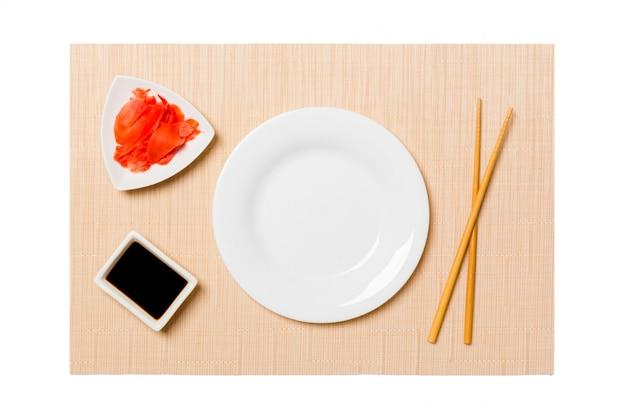 茶色の寿司マットの背景に寿司、生mat、醤油の箸で空の楕円形の白いプレート