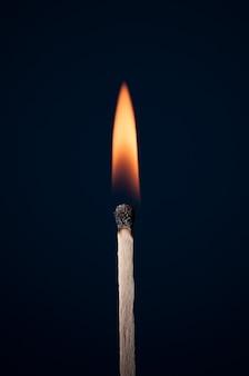 Match burning on a dark background