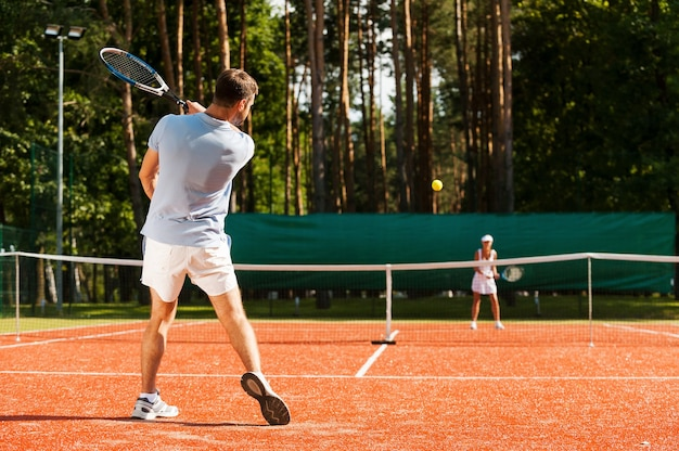 Match point. full length of man and woman playing tennis on tennis court