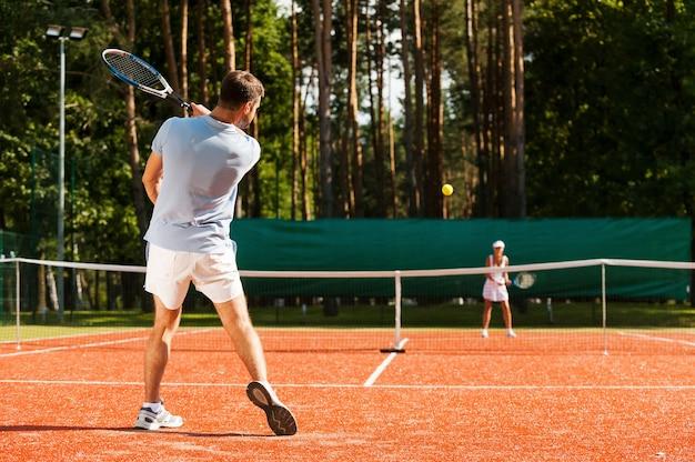 매치 포인트. 테니스 코트에서 테니스를 치는 남녀의 전체 길이