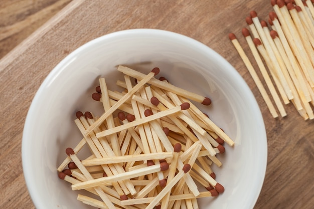 Match sticks in the ceramic bowl on the wooden table.