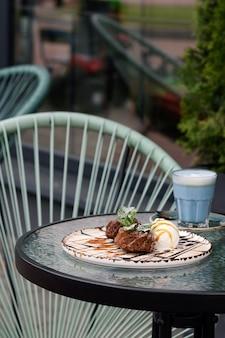 Матча и сливочный пирог на фоне кафе.
