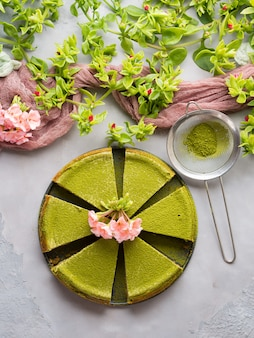 Matcha baked cheese cake and pink flowers on gray concrete