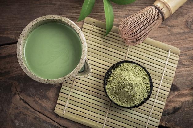 Маття измельченный зеленый чай на деревянных фоне.