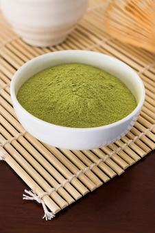 Матча тонко напудренный зеленый чай на деревянный стол в мягком фокусе в фоновом режиме.