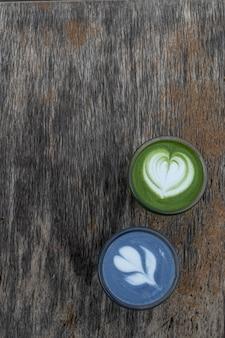 Латте с зеленым и синим чаем матча в чашках. здоровый напиток. традиционный японский напиток на черном деревянном фоне. место для текста.