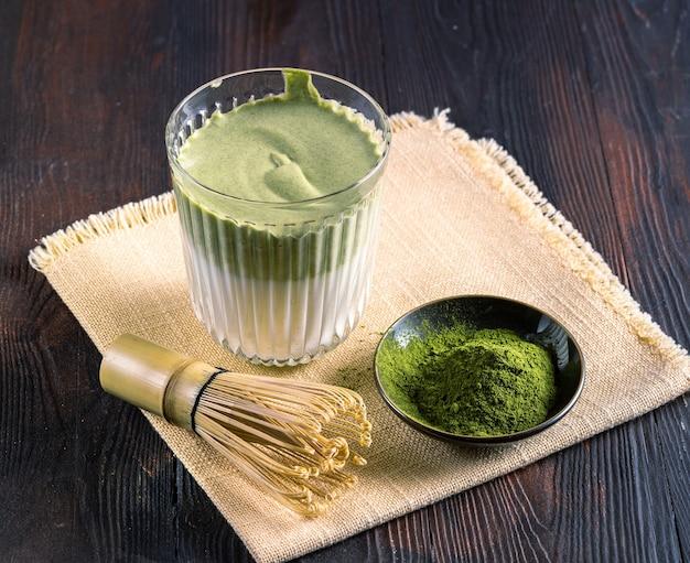 Зеленый латте чай матча, порошок матча и бамбуковый венчик на деревянном фоне, вертикальный.