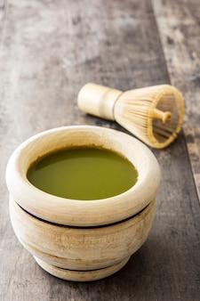 Matcha green tea in a bowl and bamboo whisk, on wooden table