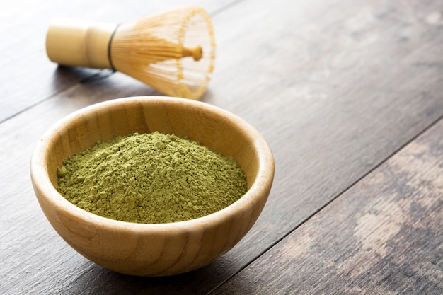 Matcha green tea in a bowl on wooden table copy space
