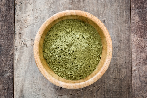 Matcha green tea in a bowl on wooden table top view