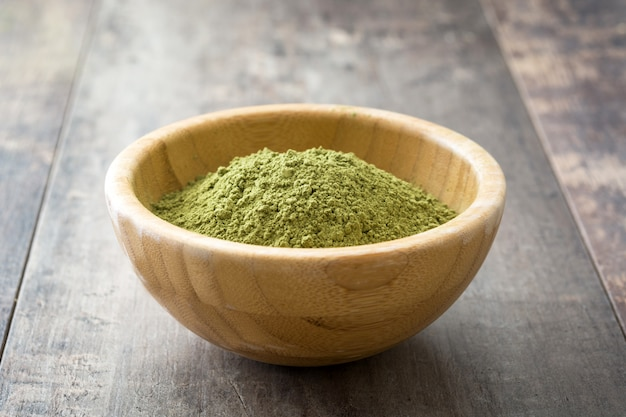 Matcha green tea in a bowl on wooden table