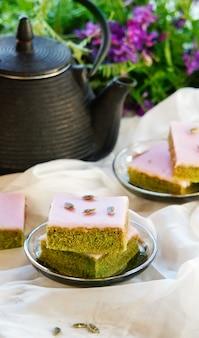 白い背景の上のお茶とホワイトチョコレート艶出し種子と抹茶グリーンティーケーキ