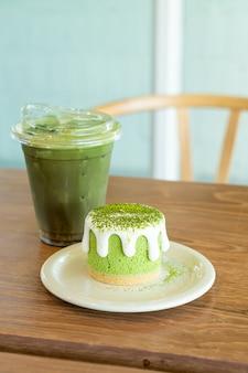 Чизкейк с зеленым чаем матча с чашкой зеленого чая на столе в кафе-ресторане