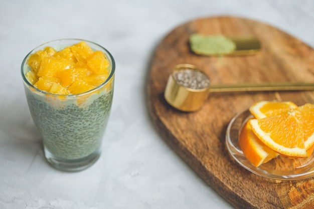 Matcha green tea chia seed pudding dessert with orange in glass